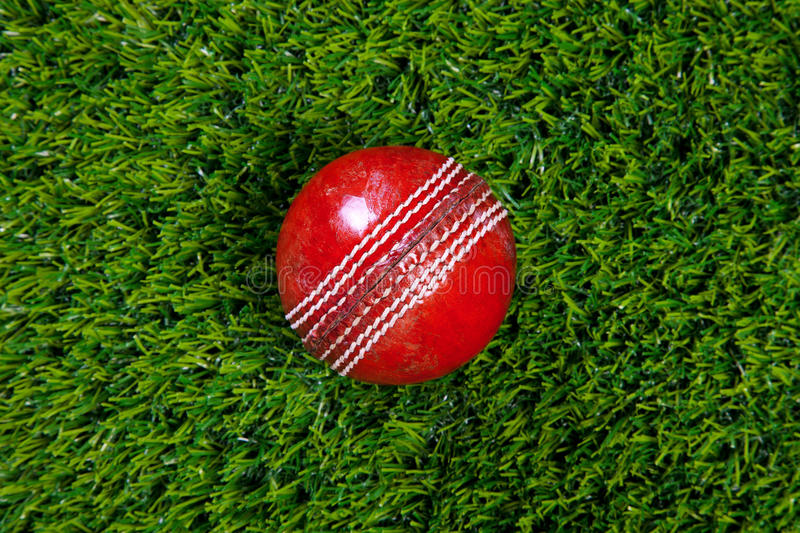 Red leather cricket ball on grass. Photo of a red leather cricket ball with stitched seams on grass stock photo