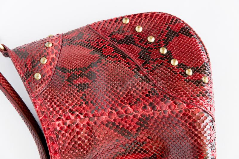 Red leather handbag made of Python skin on a white background. Fashion women`s accessories. The view from the top. Python skin. Red clutch. Leather bag. Red royalty free stock images