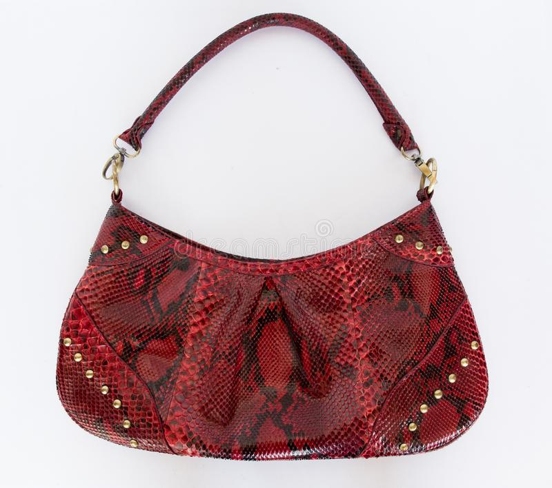 Red leather handbag made of Python skin on a white background. Fashion women`s accessories. The view from the top. Python skin. stock images