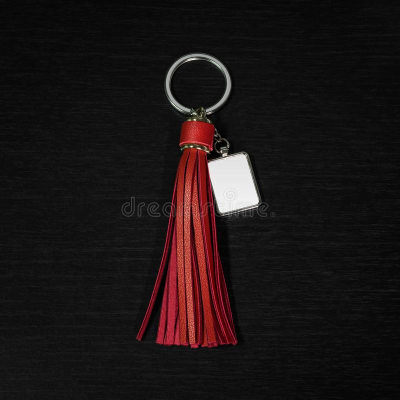 Red Leather Tassel key ring on black wooden background. Fashion leather key chain for decoration. Red Leather Tassel key ring on black wooden background. Fashion royalty free stock photography