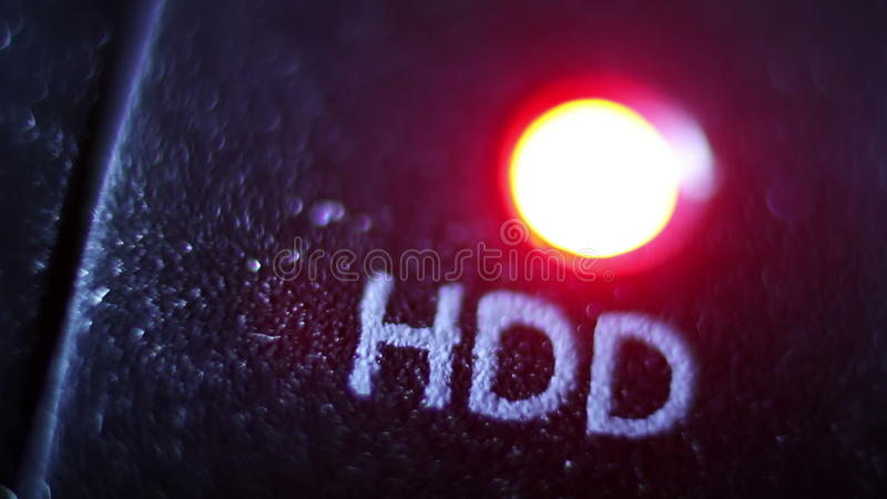 Red LED status lamp blinking through recording data on pc hard drive, close  up