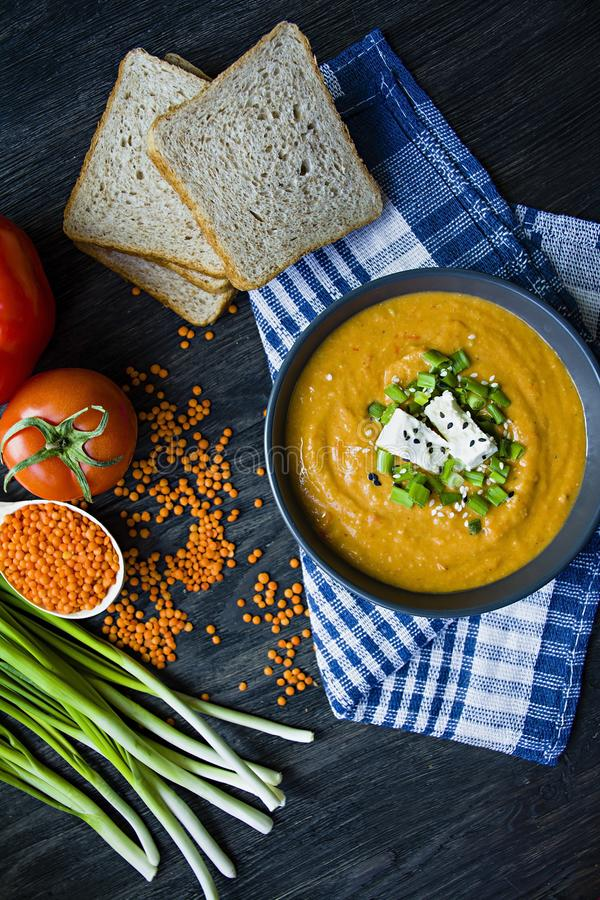 Red lentil cream soup decorated with fresh vegetables and greens. Veggie concept. Proper nutrition. View from above. Vegetarian cuisine royalty free stock image
