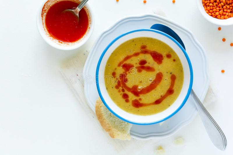 Red lentil soup with chilli pepper sauce and bread on white wooden table stock image