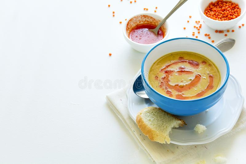 Red lentil soup with chilli pepper sauce and bread on white wooden table royalty free stock image