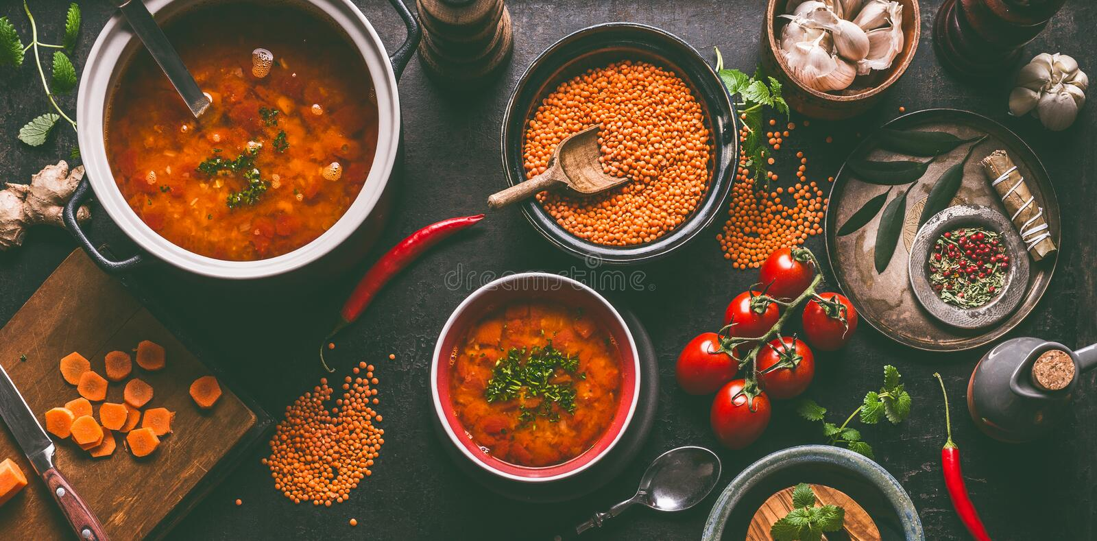 Red lentil soup with cooking ingredients on dark rustic kitchen table background, top view. Healthy vegan food concept. Vegetarian royalty free stock images