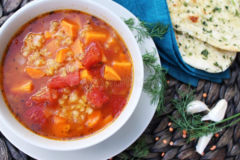 Red lentil soup served with naan bread royalty free stock photo