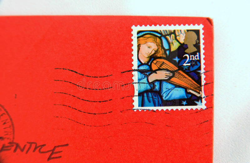 Red letter day ?. A canceled second class postage stamp with an angel on it stuck to a red envelope and bearing a christmas card stock photo