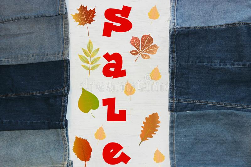 The word clearance surrounded by yellow leaves. Red letters, the word sale on white background, frame textiles, denim fabric stock photography