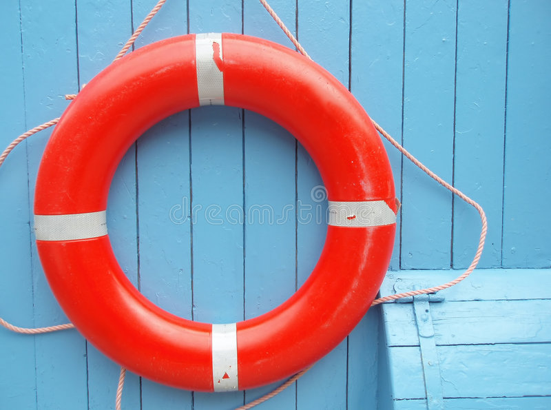Red life buoy. Hanging on a clear blue wall stock photography