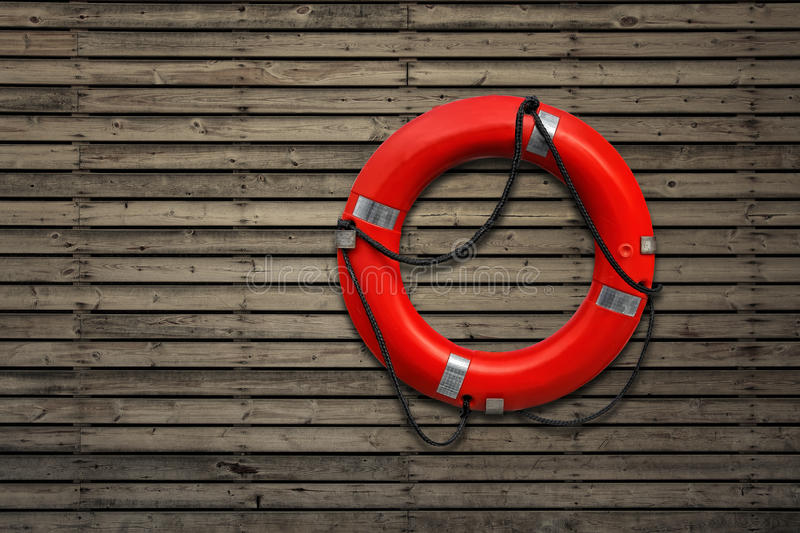 Red life buoy. On a wooden wall royalty free stock image