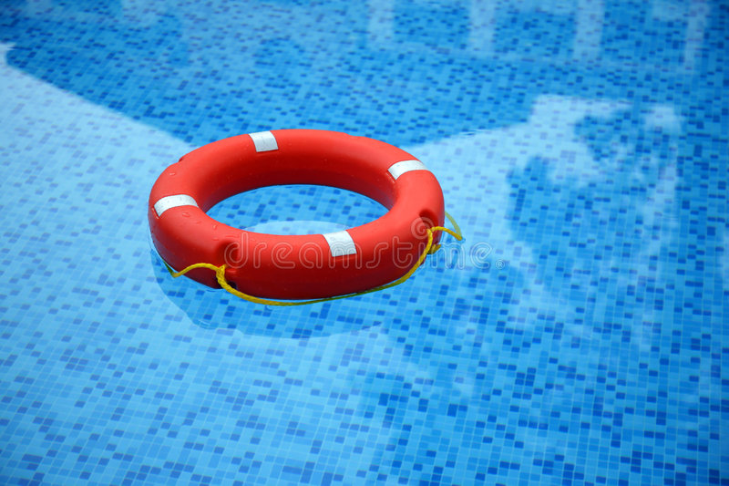Red life buoy. Floating in swimming pool royalty free stock photos