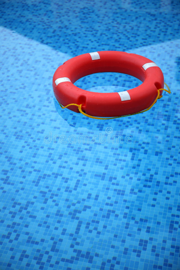 Red life buoy. Floating in swimming pool stock image