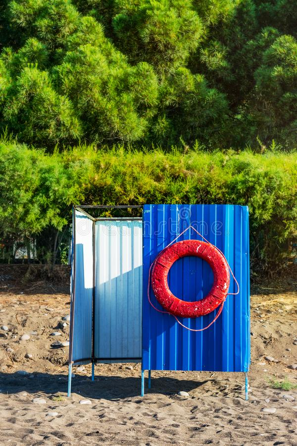 Red life buoy. Hanging on blue beach cabana. Save life concept royalty free stock photography