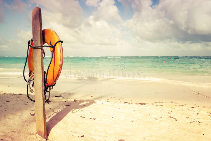 Red life buoy hanging on wooden pole. Empty sunny sandy beach landscape, Dominican republic. Vintage toned photo filter with old style effect royalty free stock photo