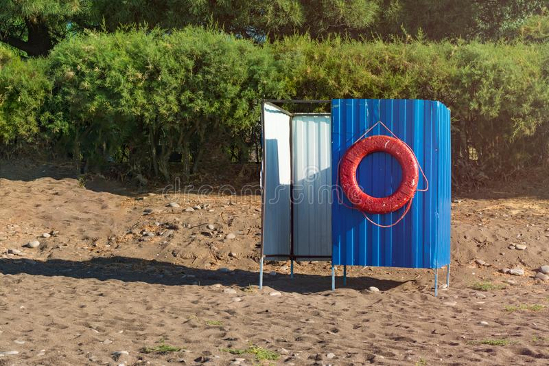 Red life buoy. Hanging on blue beach cabana. Save life concept stock images