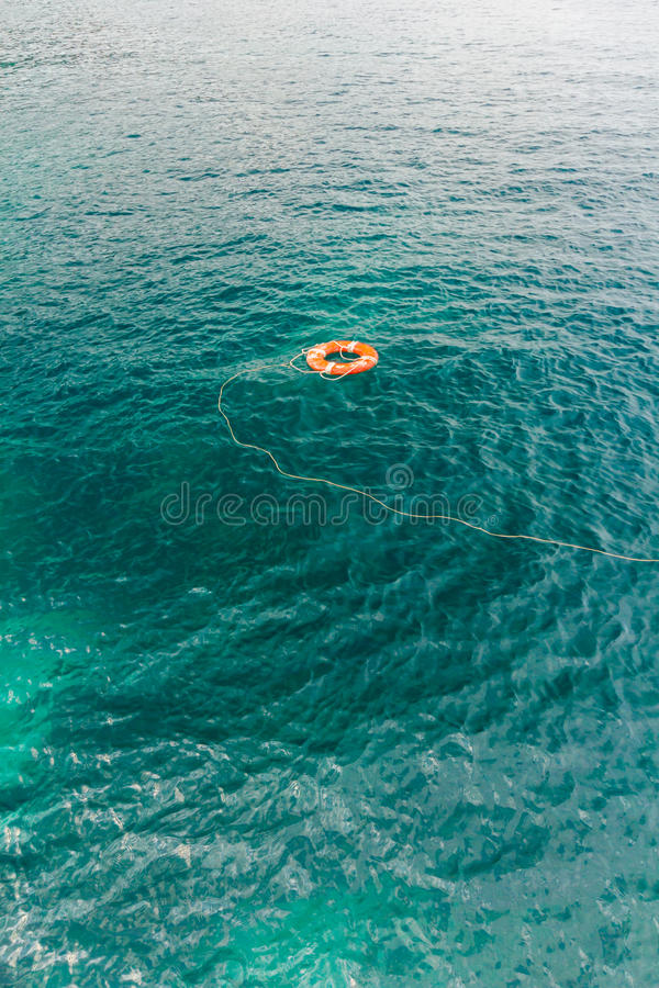 Red life buoy in the water. Safe water support aid circle with rope. Rescue red life buoy on wooden background of ship or boat. Helpful object stock images
