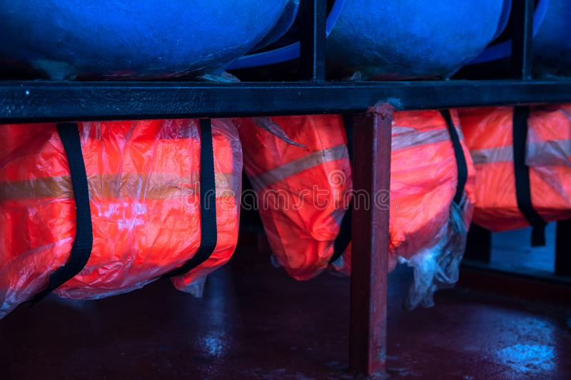 Red life jacket under blue plastic chair. Ferry safety equipment closeup. Life saving appliance in ship cabin royalty free stock photo