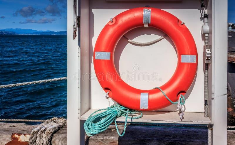 Red life saving buoy near the ocean royalty free stock photo