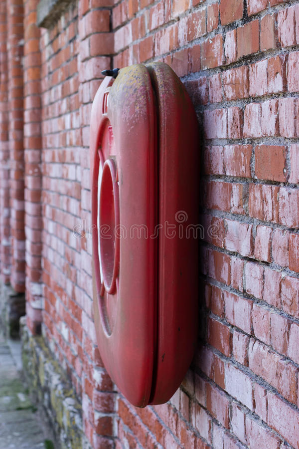 A red lifebelt on a red brick wall. A red lifebelt against a weathered red brick wall royalty free stock photography