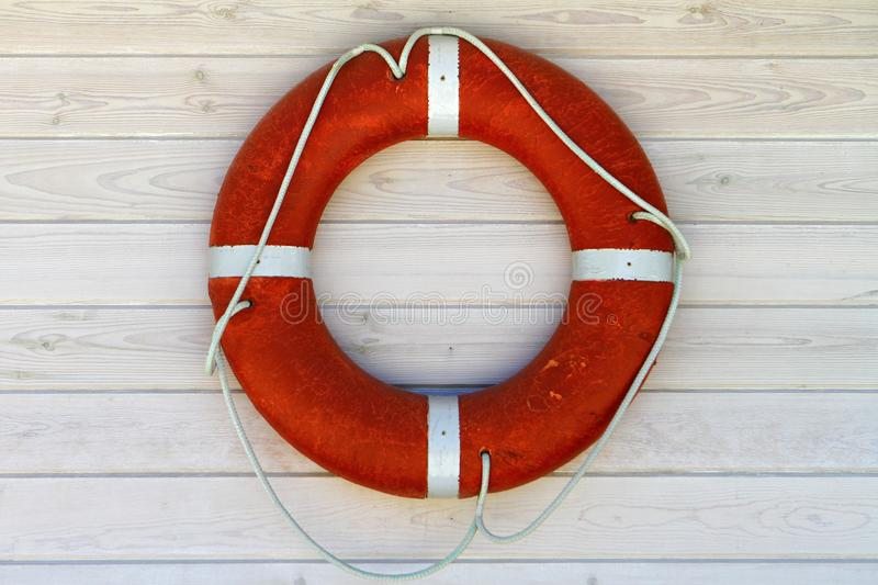 Red lifebuoy on the white wood painted wall background stock photos