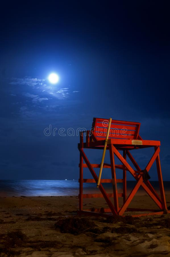 A red lifeguard stand on the beach at night. A red lifeguard stand on the beach on Amelia Island, Florida, by the light of the full moon and lightpainting royalty free stock image
