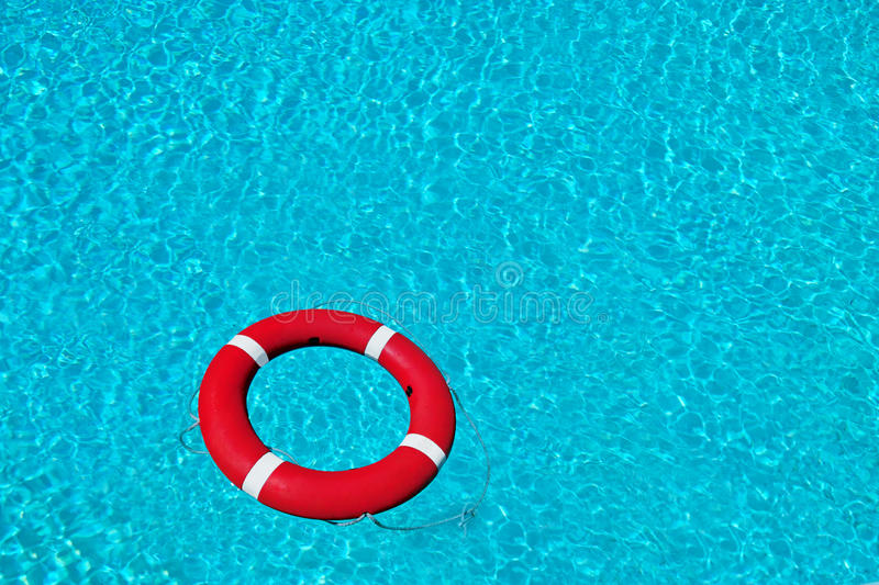 Red lifesaving buoy on beautiful deep water. Red-white lifesaving buoy on the beautiful deep blue water. There are bright waves reflection on it. The surface of royalty free stock photo