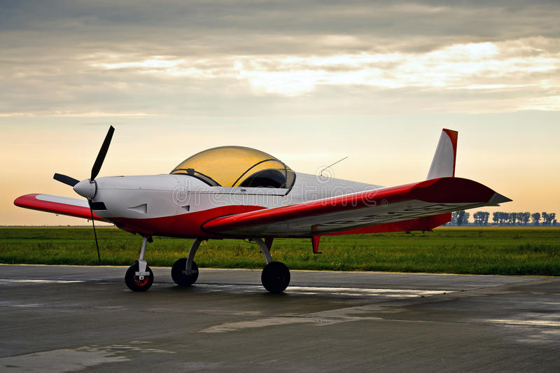 Red light aircraft in sunrise light. A light single-engine aircraft in sunrise crepuscular light stock images