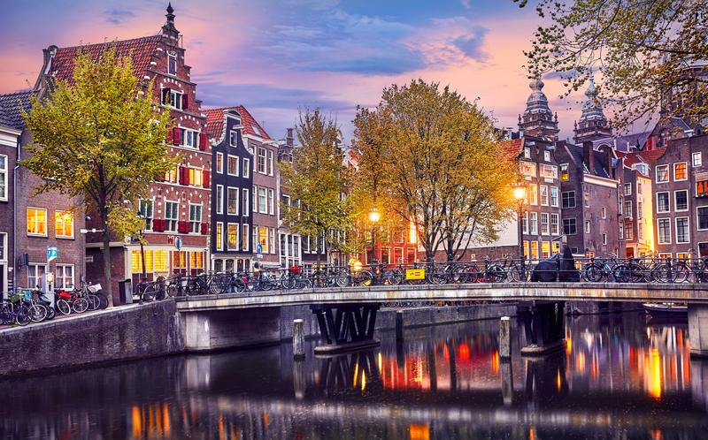 Red-light district in Amsterdam city picturesque landscape panorama evening town with pink sunset sky. Bridge over canal river stock image