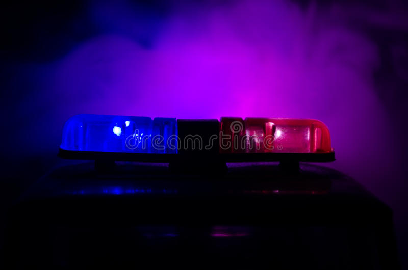 Red light flasher atop of a police car. City lights on the background. Police government concept stock images