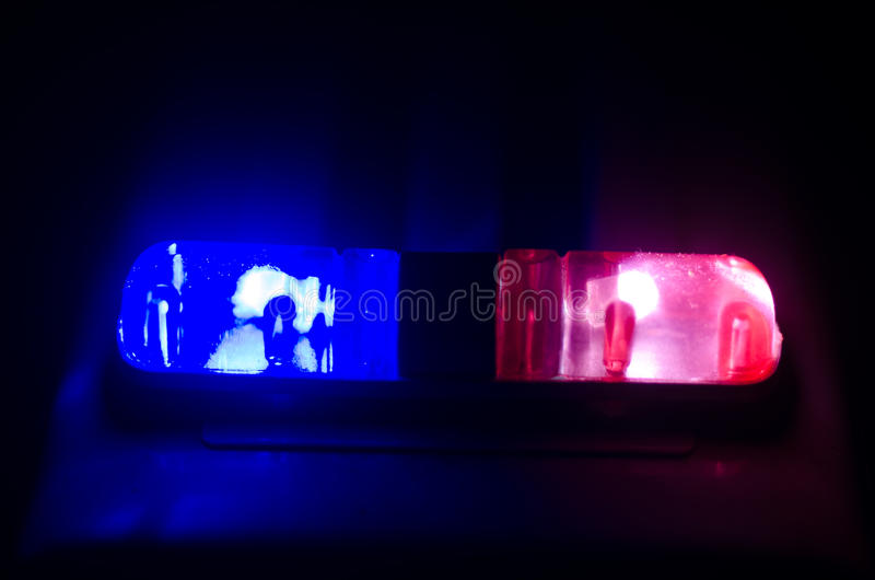 Red light flasher atop of a police car. City lights on the background. Police government concept. Red light flasher atop of a police car. City lights on the stock photography
