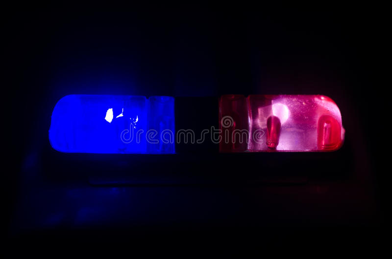 Red light flasher atop of a police car. City lights on the background. Police government concept. Red light flasher atop of a police car. City lights on the stock image