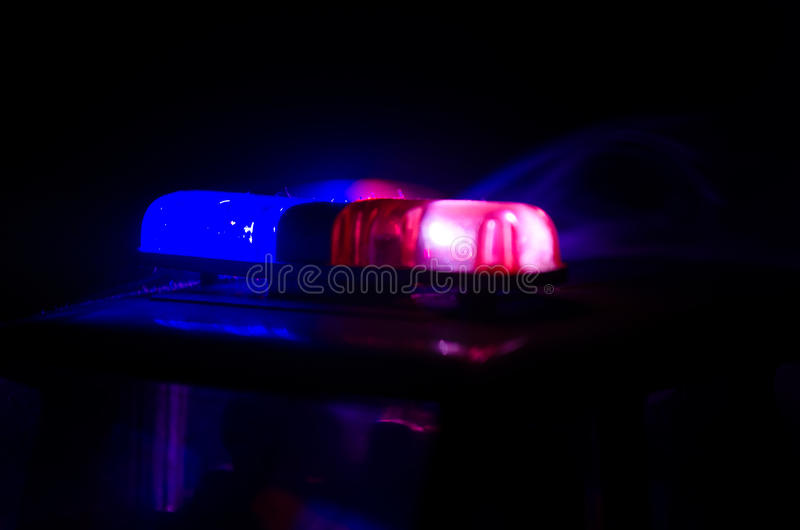 Red light flasher atop of a police car. City lights on the background. Police government concept. Red light flasher atop of a police car. City lights on the stock photos