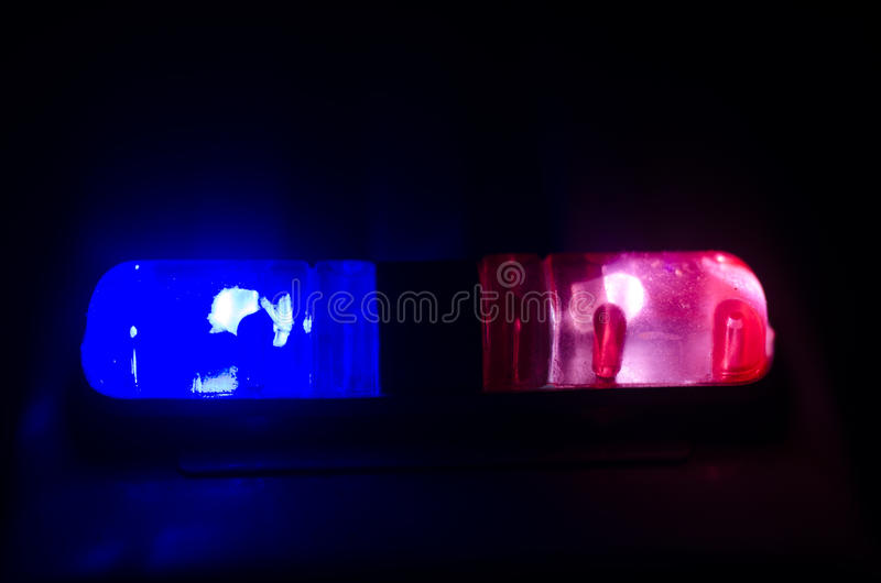Red light flasher atop of a police car. City lights on the background. Police government concept stock photos