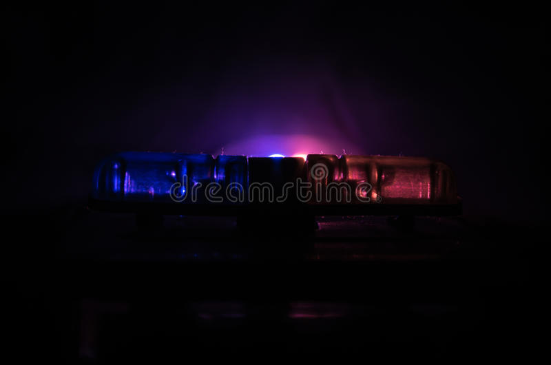 Red light flasher atop of a police car. City lights on the background. Police government concept stock image