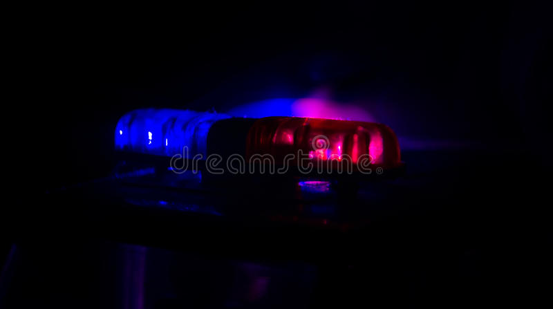 Red light flasher atop of a police car. City lights on the background. Police government concept royalty free stock photos