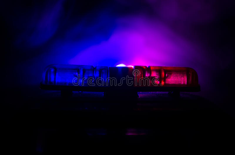 Red light flasher atop of a police car. City lights on the background. Police government concept royalty free stock image