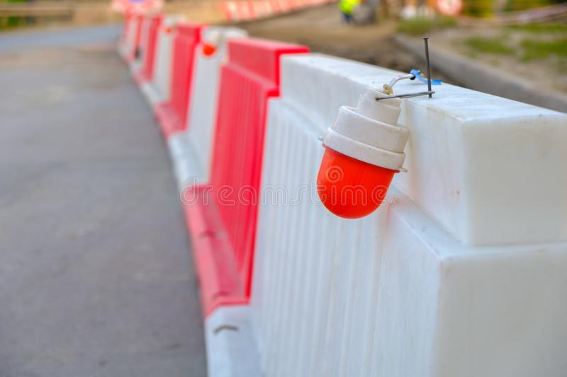The red light on the plastic enclosure during the repair of the bridge, stretching into the distance. Plastic temporary fence royalty free stock photo