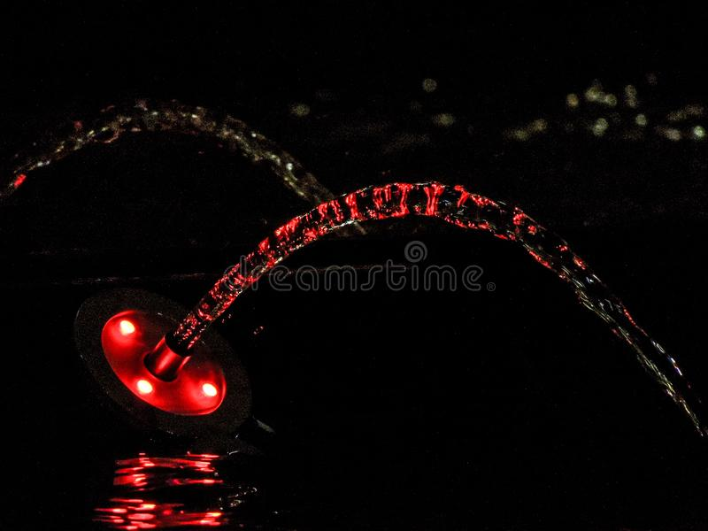 Red-lighted water gush. At fountain at night reflected on the fountain`s water shot at night stock photos