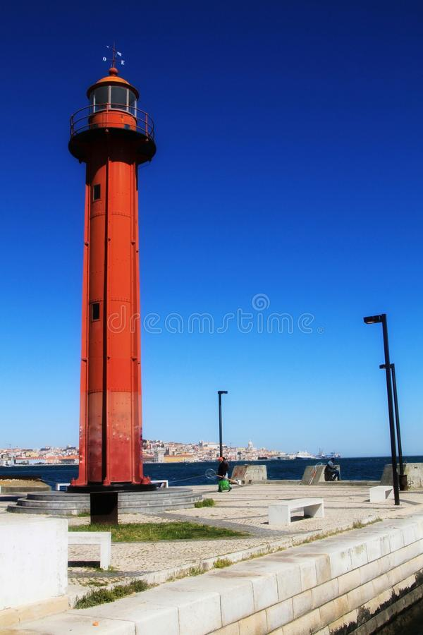 Red lighthouse in the port of Almada village in Lisbon royalty free stock photo