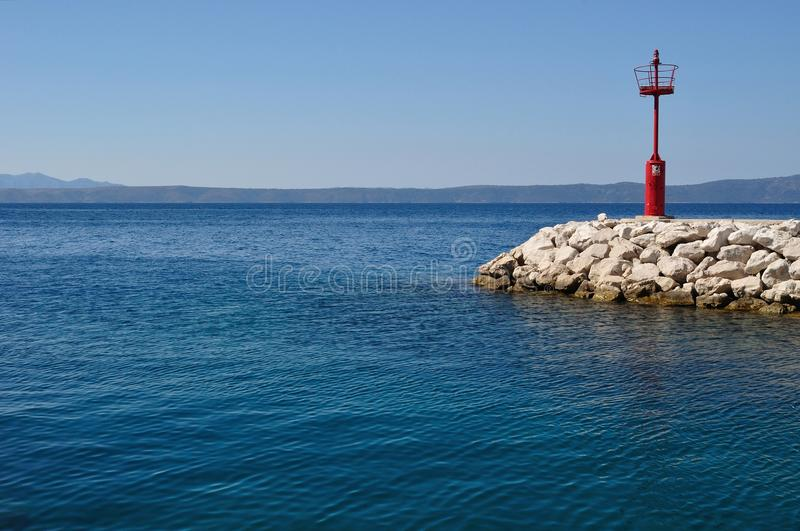 Red lighthouse in port with stones royalty free stock photo