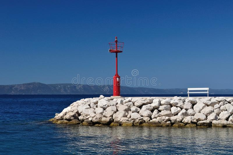 Red lighthouse in port with stones and white bench. Podgora, Croatia stock image
