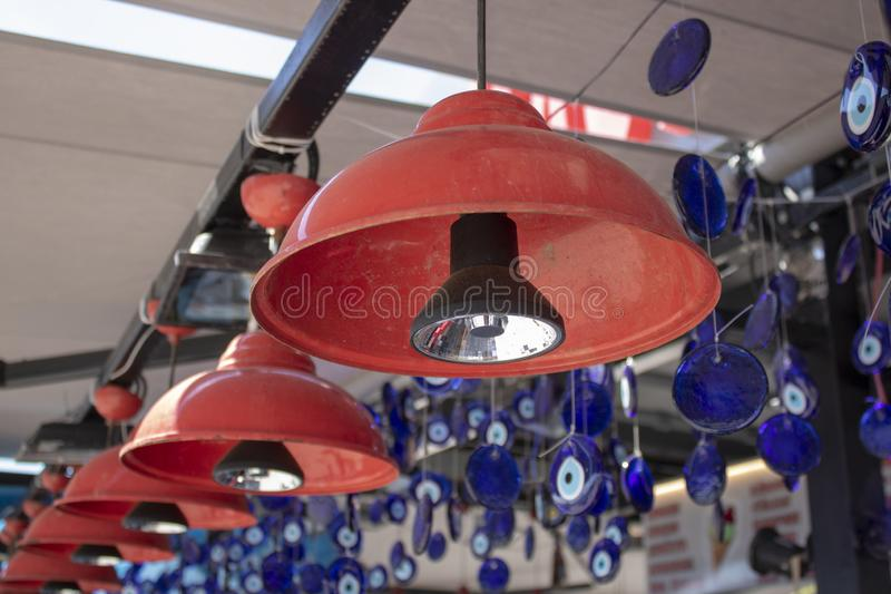 Red lightings hanging in front of store. Conical shape. Evil eye beads are in the background. Lamp, dusty, eyes, shop, outdoor, interior, wall, room, design stock image