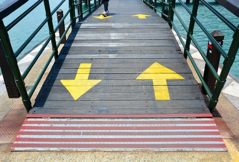 Red line at the start-end point and two way yellow traffic arrows sign on wooden bridge royalty free stock image
