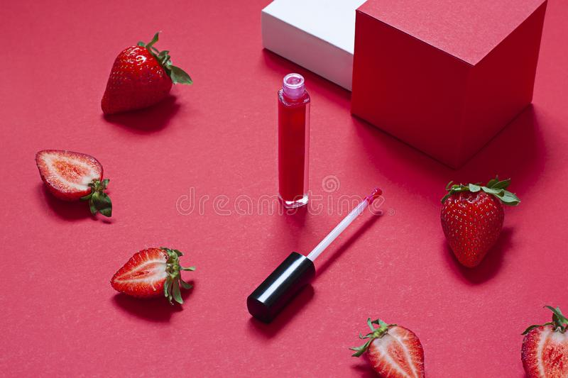 Red lip gloss beauty concept close up with fresh strawberries. On the red background royalty free stock photo
