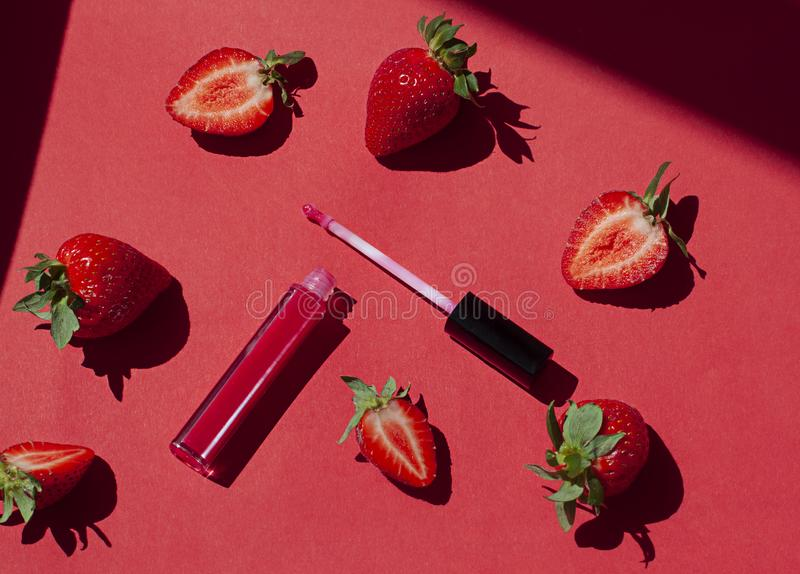 Red lip gloss beauty concept flat lay with fresh strawberries on the red. Background stock photos