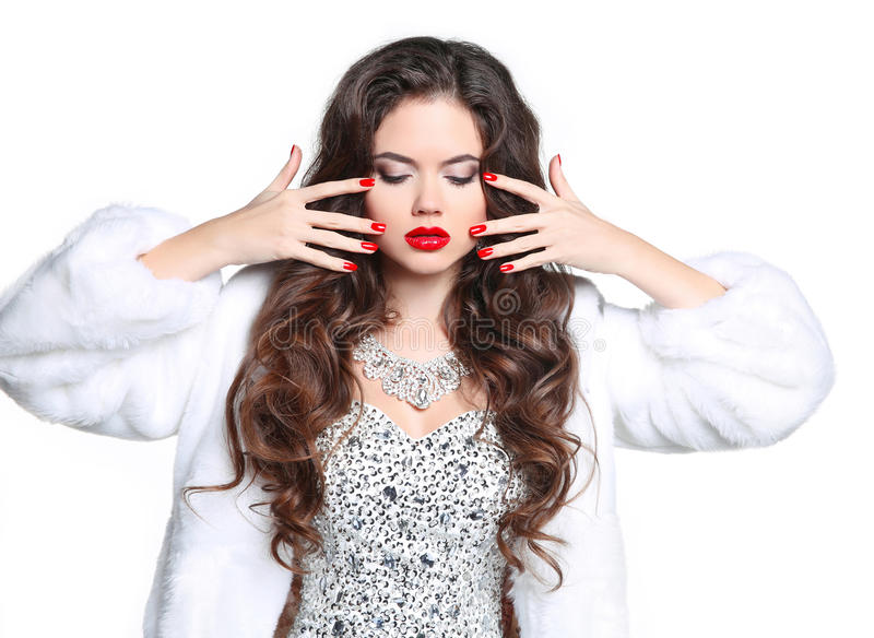 Red lips and manicured nails. Winter Brunette Woman in Luxury white mink Fur Coat. Beauty Fashion Model Girl in beaded and sequin royalty free stock image