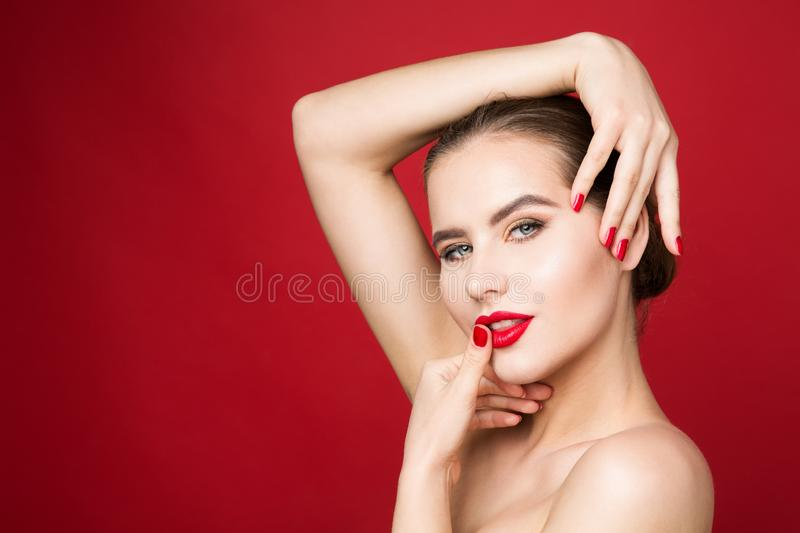 Red Lips and Nails, Woman Beauty Make Up, Red Lipstick and Polish, Beautiful Girl Face Makeup. On red background royalty free stock photos