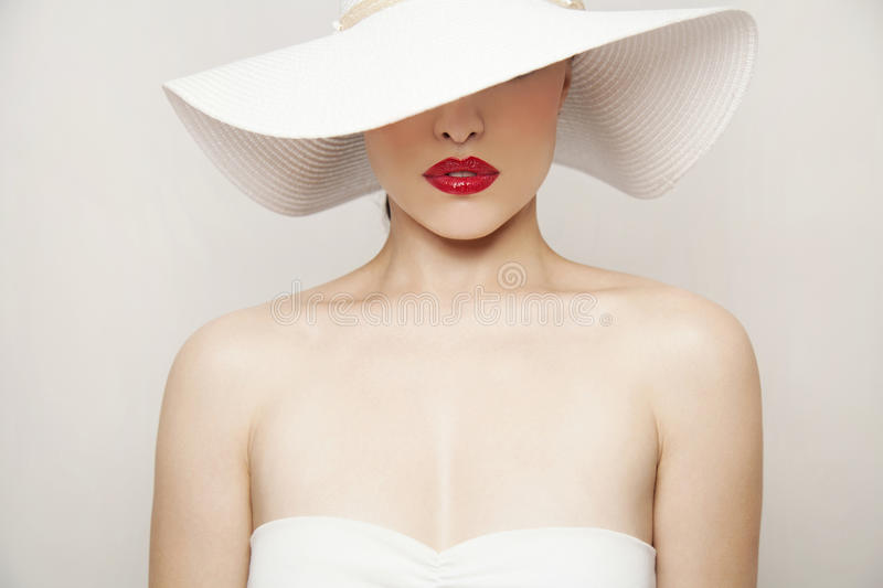 Red lips and white hat. Woman beauty portrait with red lips and summer white hat, studio royalty free stock image