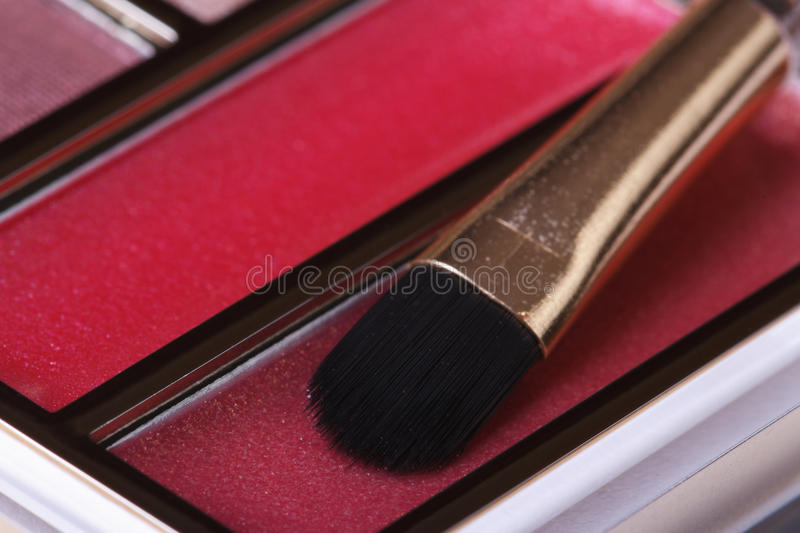 Red lipstick with applicator in a set of cosmetics close up. Macro royalty free stock images