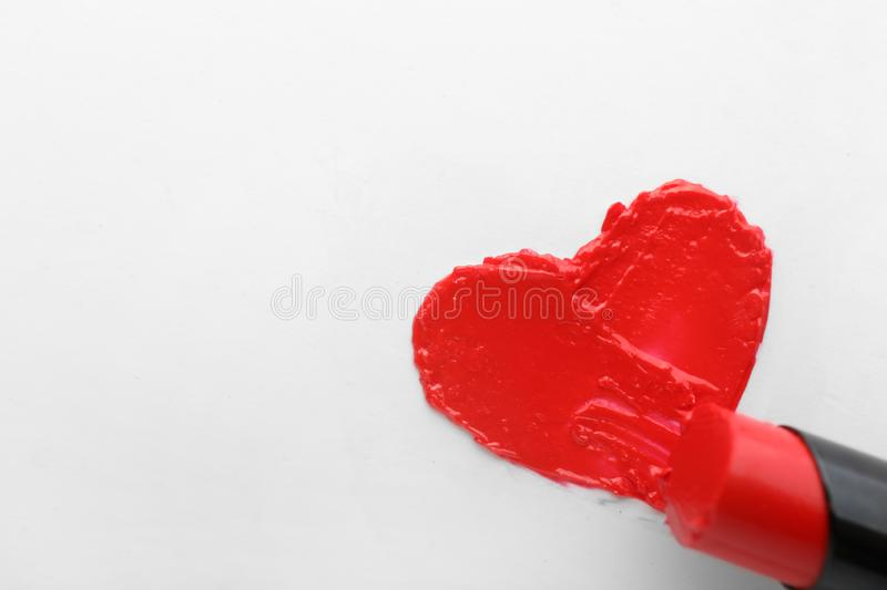 Red lipstick with drawn heart on white background stock image